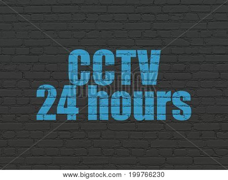 Protection concept: Painted blue text CCTV 24 hours on Black Brick wall background