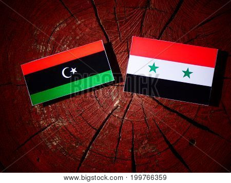 Libyan Flag With Syrian Flag On A Tree Stump Isolated
