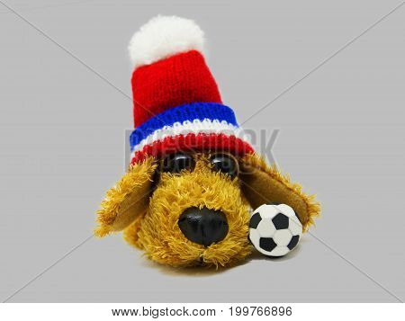 Toy dog with a soccer ball on a gray background