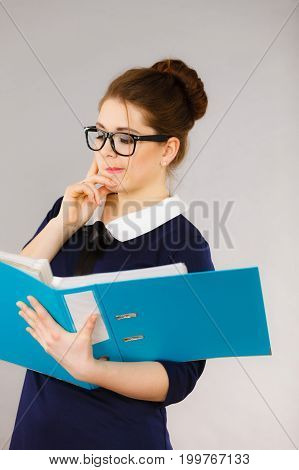 Woman office worker agent holding blue file folder in hands. Young elegant businesswoman or secretary with documents bills. Thinking face expression. Business and paperwork on grey