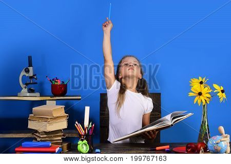 Schoolgirl With Proud Face Holds Big Book And Pencil Up