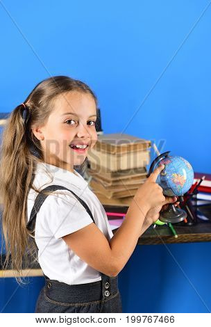 Schoolgirl With Interested Face Points At Little Globe