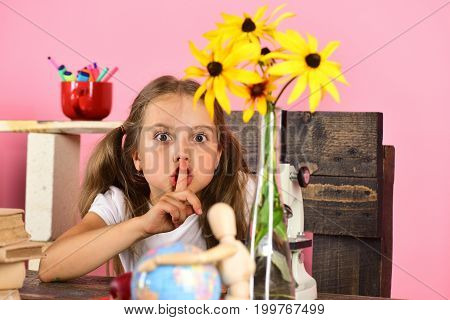 Kid and school supplies on pink background. Back to school and natural beauty concept. Girl with concerned face makes silence warning gesture. Schoolgirl at desk with yellow flowers globe and books