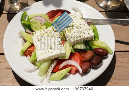 Village greek salad in greek tavern. Horizontal. Daylight. Close-up