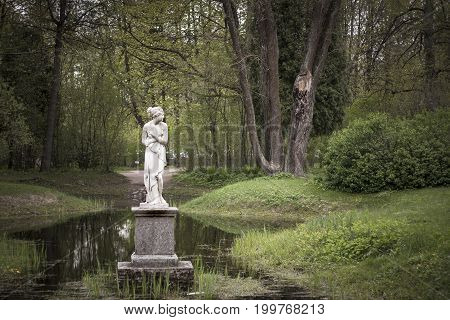 Shy woman sculpture in park. Classic monument of timidity.