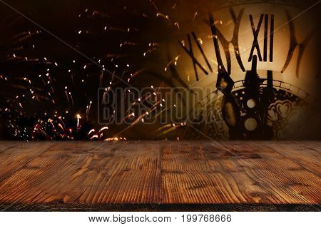 Night sky with fireworks and a clock in front of a wooden stage for a new year or christmas concept