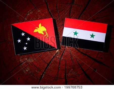 Papua New Guinea Flag With Syrian Flag On A Tree Stump Isolated