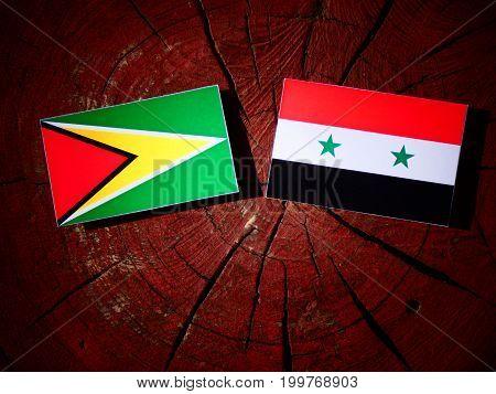 Guyana Flag With Syrian Flag On A Tree Stump Isolated