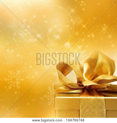 Golden gift with a loop in front of a christmas background with stars and bokeh