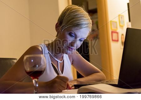 woman writing notes from laptop while she is drinking wine