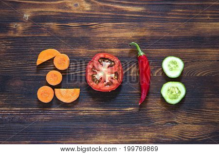 happy new year 2018 made of vegetables on wooden background