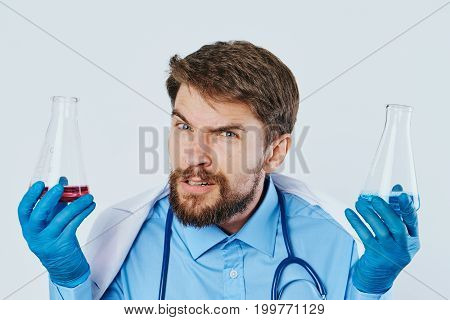 A man with a beard on a light background holds laboratory utensils, science, scientist, doctor, medicine.