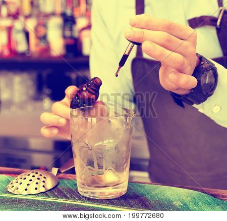 Bartender is dropping bitter into mixing glass, toned image