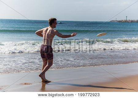 Teenagers Beach Frisby Throwing