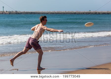 Teenager Beach Frisby Throwing
