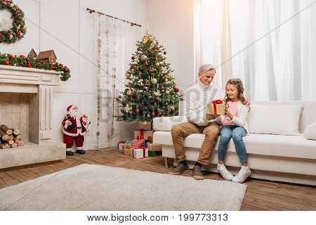 Grandfather Presenting Gift To Granddaughter