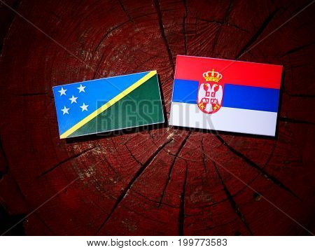 Solomon Islands Flag With Serbian Flag On A Tree Stump Isolated