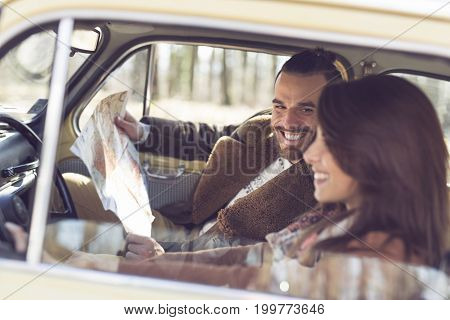Young couple having fun and enjoying a road trip. Girl driving a car while the guy is sitting and looking at the map