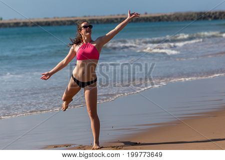 Teenager girl throwing frisby on beach ocean waterline.