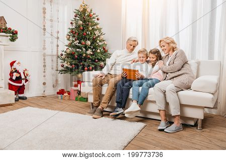Grandparents And Kids Looking At Tablet