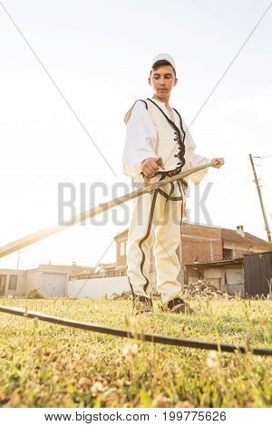 young man in traditional costume mow the grass with scythe in the old way