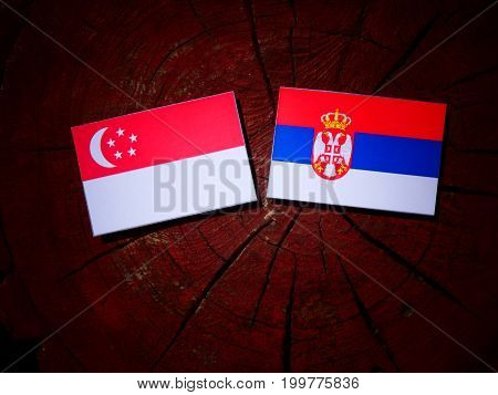 Singaporean Flag With Serbian Flag On A Tree Stump Isolated