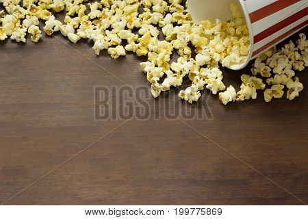 Red and white striped  box of popcorn for movie on wooden background ,Popcorn frame on wooden background