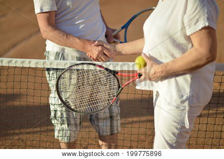 Cropped image of senior couple shaking hands over net after tennis game