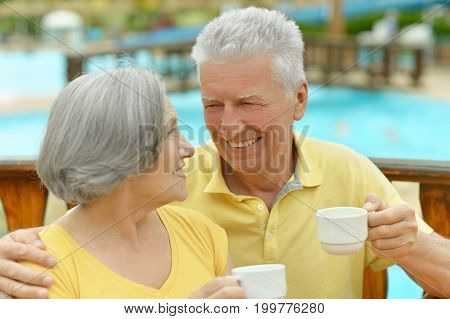Smiling senior couple drinking coffee on blurred background