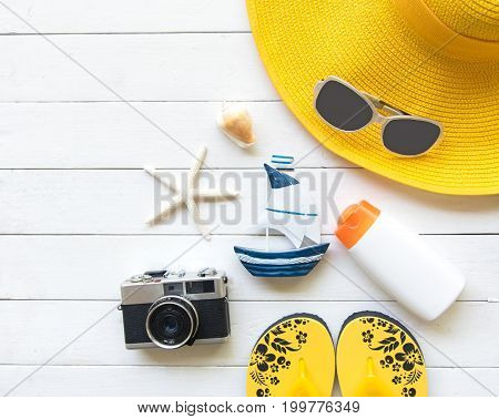 Summer Fashion woman yellow big hat and accessories in the beach. Tropical sea.Unusual top view wood white background. Summer Concept.