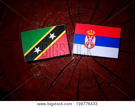 Saint Kitts And Nevis Flag With Serbian Flag On A Tree Stump Isolated