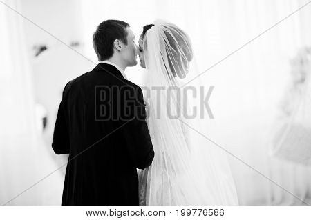 Gorgeous Wedding Couple Enjoying Each Other's Company In Front Of A Mirror. Black And White Photo.