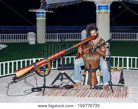 Nahariya Israel August 14 2017 : A young guy plays a guitar in the evening on the waterfront in the city of Nahariya in Israel