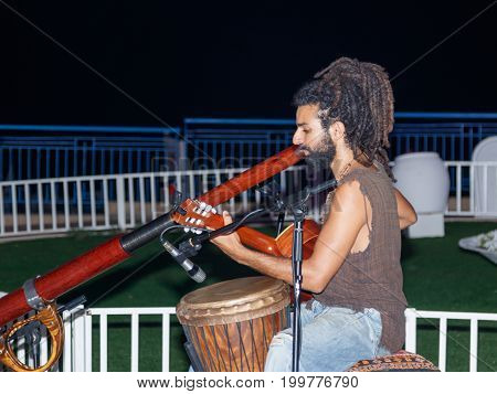 Nahariya Israel August 14 2017 : A young guy plays a guitar and a big pipe in the evening on the waterfront in the city of Nahariya in Israel