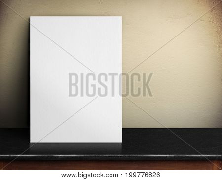 Blank White Paper Poster On Black Marble Table At Yellow Concrete Wall,template Mock Up For Adding Y