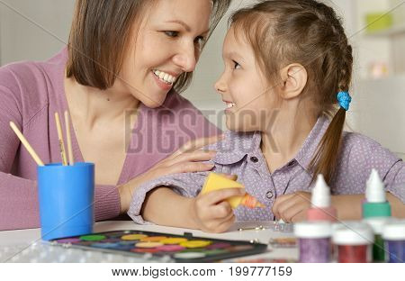 Young mother and daughter sitting at table and playing together
