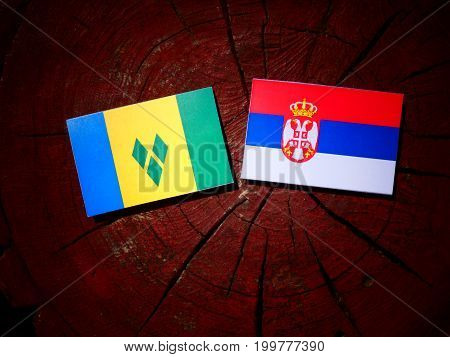 Saint Vincent And The Grenadines Flag With Serbian Flag On A Tree Stump Isolated
