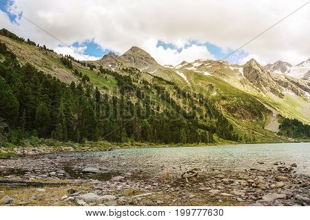 Clear River With Rocks Leads Towards Mountains