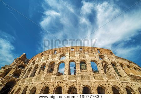 View outside the Colosseum Rome Italy with specific ruins and sky with clouds in background.