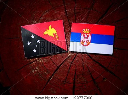Papua New Guinea Flag With Serbian Flag On A Tree Stump Isolated