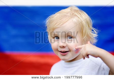 Portrait Of Cute Little Boy With Russian Flag On Background