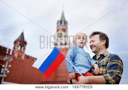 Middle Age Man And His Little Son With Russian Flag With Spasskaya Tower (russia, Moscow) On Backgro