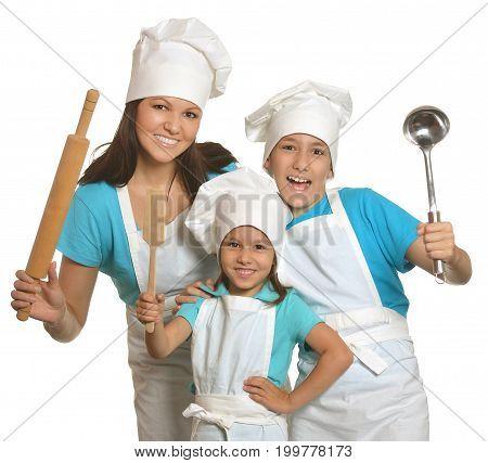 Mother and children in chefs uniform with kitchen utensils