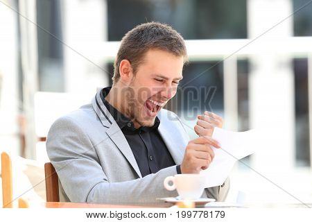 Excited executive reading a letter sitting in a coffee shop