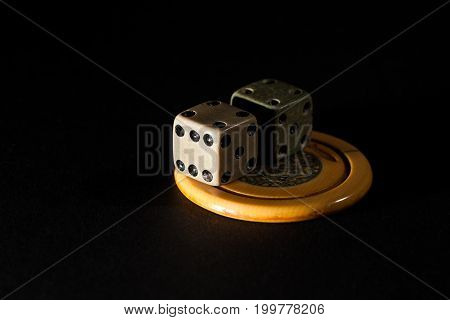 Pair of vintage gambling dice and casino poker chip lucky charms in auspicious lighting.