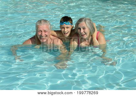 grandparents with grandson in swimming pool, smiling and posing poster