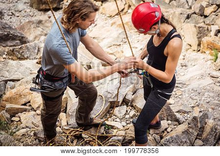 Two young climbers checking each other's equipment