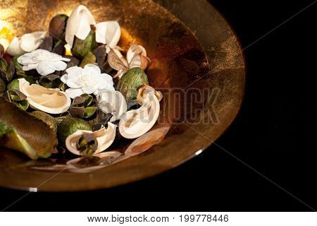 Ornamental fragrant potpourri in decorative gold leaf bowl. Home decor accessory. Black background with copy space.