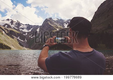 Man Hands Holding Mobile Phone At Sea And Mountains