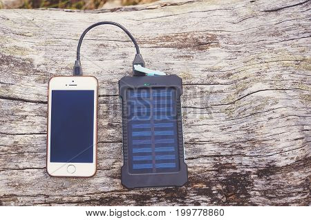 Smartphone Charging With Pink Power Bank On Wood Background
